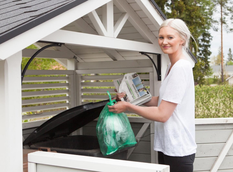 Nainen laittamassa roskapussia jäteastiaan.